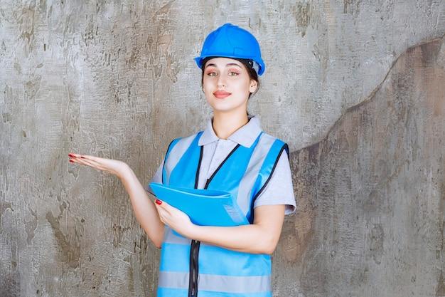 파란색 제복을 입은 여성 엔지니어와 파란색 보고서 폴더를 들고 주위 사람을 가리키는 헬멧.
