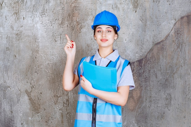 青い制服と青いレポートフォルダーを保持し、周りの誰かを指しているヘルメットの女性エンジニア