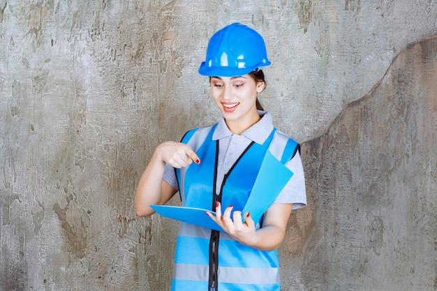 파란색 제복을 입은 여성 엔지니어와 파란색 보고서 폴더를 들고 있는 헬멧