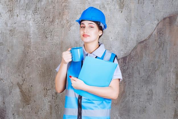 青いティーカップと青いレポートフォルダーを保持している青い制服とヘルメットの女性エンジニア。