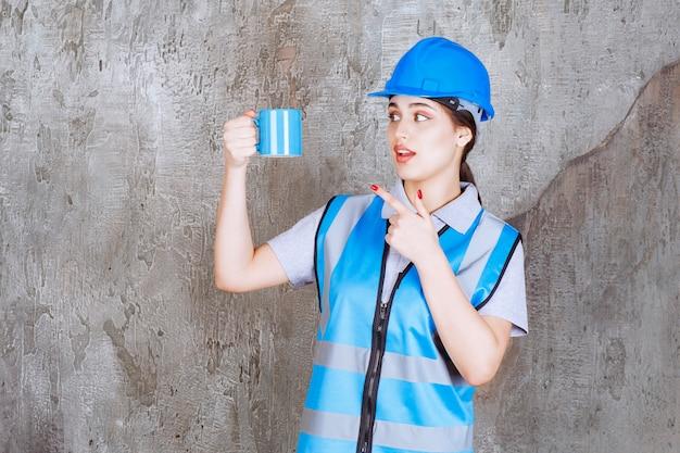 青い制服と青いティーカップを保持しているヘルメットの女性エンジニア。
