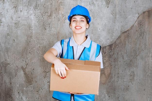 파란색 유니폼과 골 판지 소포를 들고 헬멧에 여성 엔지니어.
