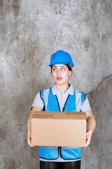 青い制服と段ボールの小包を保持しているヘルメットの女性エンジニア。