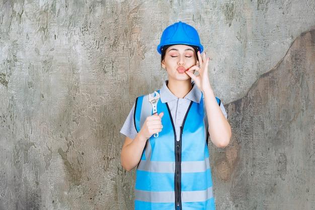 Женщина-инженер в синей форме и шлеме держит металлический ключ и показывает положительный знак руки.
