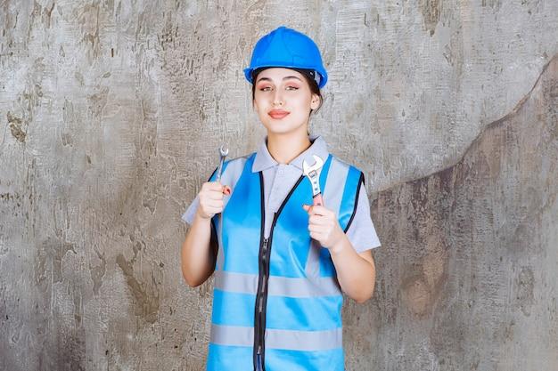 青い制服と金属レンチを保持しているヘルメットの女性エンジニア。