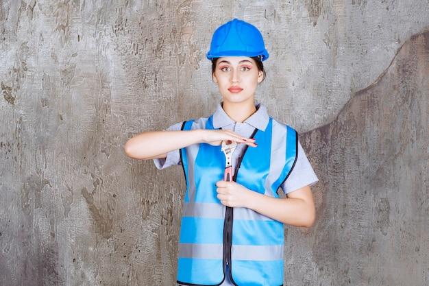 青い制服と金属レンチを保持しているヘルメットの女性エンジニア