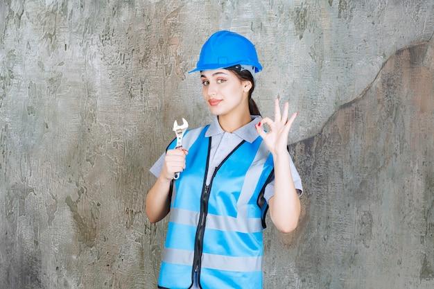 Женский инженер в синей форме и шлеме держит металлический ключ.