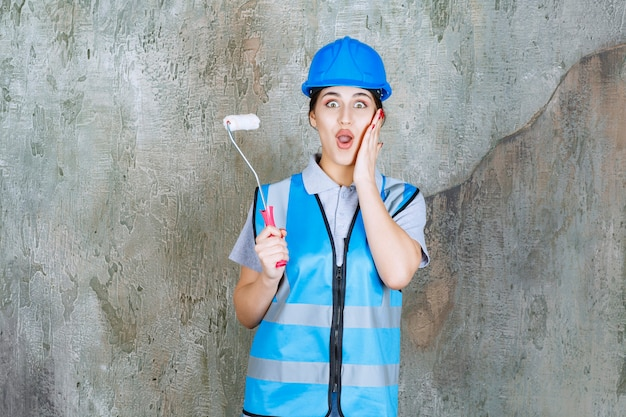 青い制服を着た女性エンジニアと、塗装用のトリムローラーを持ったヘルメットが怖くて怖いように見えます。