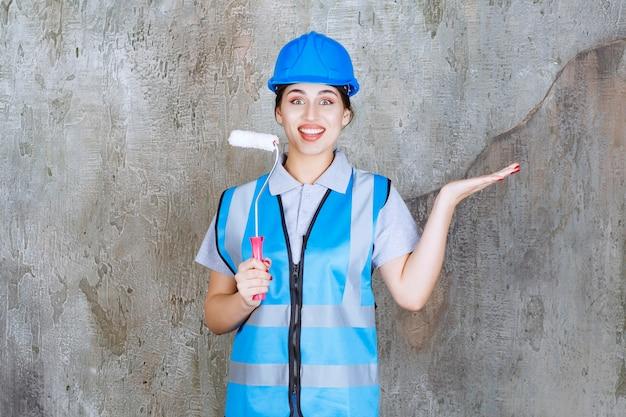 青い制服を着た女性エンジニアと、後ろのコンクリートの壁をペイントして指すためのトリムローラーを持ったヘルメット。