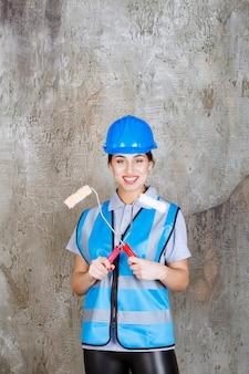 Женщина-инженер в синей форме и шлеме держит обрезной валик для покраски.