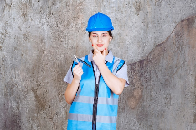 파란색 유니폼과 헬멧 수리를 위해 금속 펜 치를 들고 여성 엔지니어와 사려 깊어 보인다.