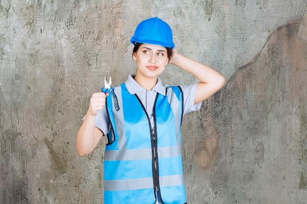 파란색 유니폼을 입은 여성 엔지니어와 수리를 위해 금속 펜치를 들고 헬멧을 쓰고 사려깊게 보입니다.