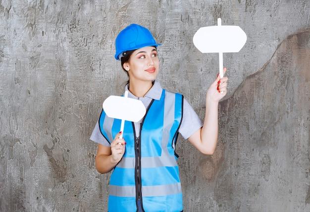 Инженер-женщина в синей форме и шлеме, держа в обеих руках две пустые информационные табло.