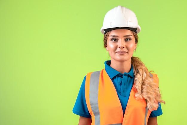 Инженер-женщина в белом шлеме и снаряжении выглядит профессионально.