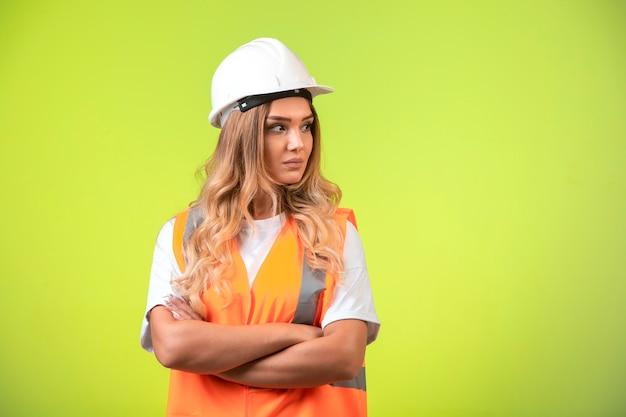 白いヘルメットとギアを担当する女性エンジニア。