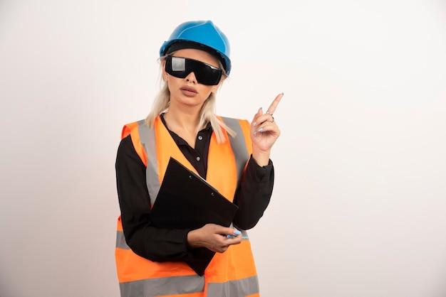 白い背景を指しているメガネの女性エンジニア。高品質の写真