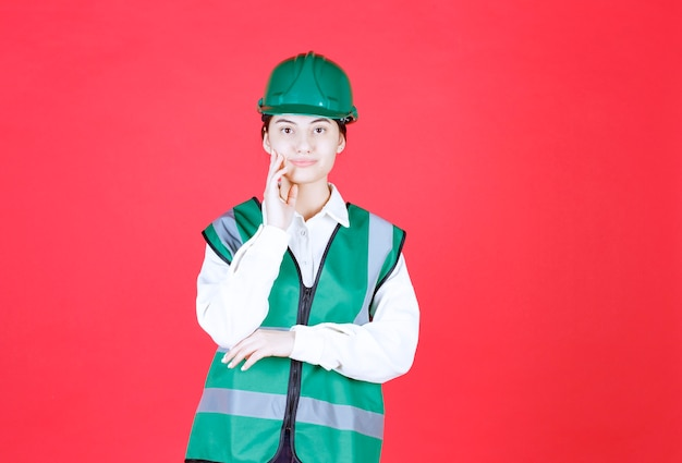 緑のヘルメットと制服を着た女性エンジニアは混乱して思慮深く見えます