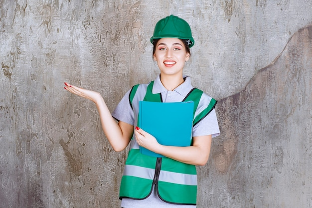 青いフォルダーを保持し、周りの誰かを指している緑のヘルメットの女性エンジニア。