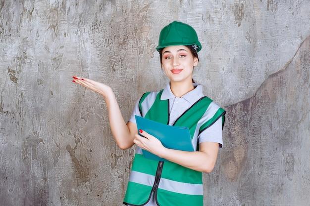 파란색 폴더를 들고 주위 사람을 가리키는 녹색 헬멧에 여성 엔지니어