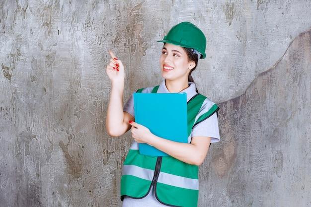 青いフォルダーを保持し、周りの誰かを指して緑のヘルメットの女性エンジニア