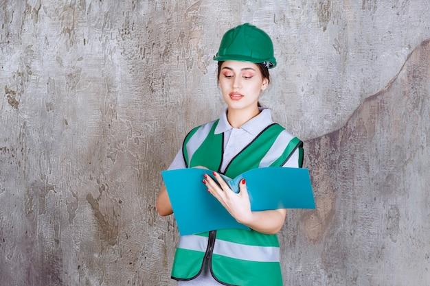 파란색 폴더를 들고 녹색 헬멧에 여성 엔지니어.