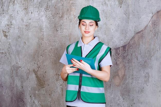 青いフォルダーを保持している緑のヘルメットの女性エンジニア。