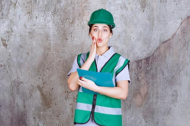青いフォルダーを保持している緑のヘルメットの女性エンジニア