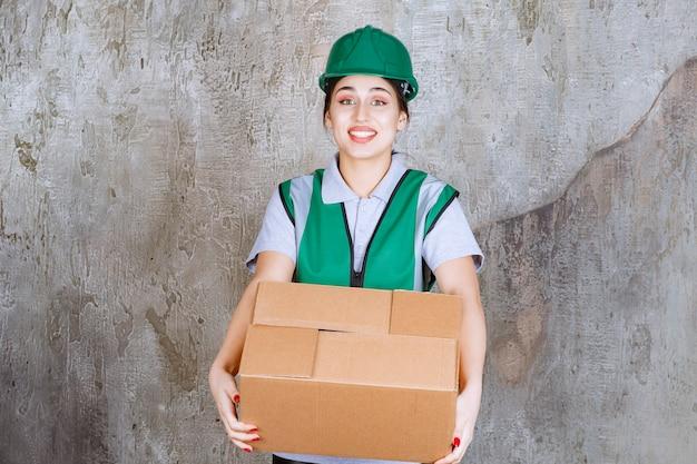 段ボール箱を保持している緑のヘルメットの女性エンジニア。