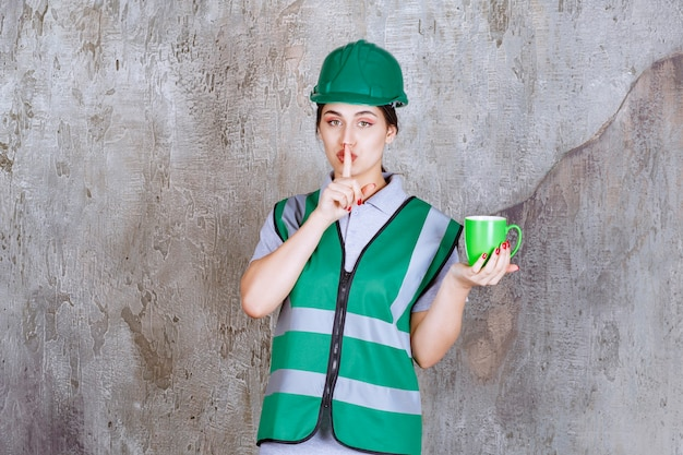 緑のコーヒーマグを保持し、沈黙を求めている緑のヘルメットの女性エンジニア。