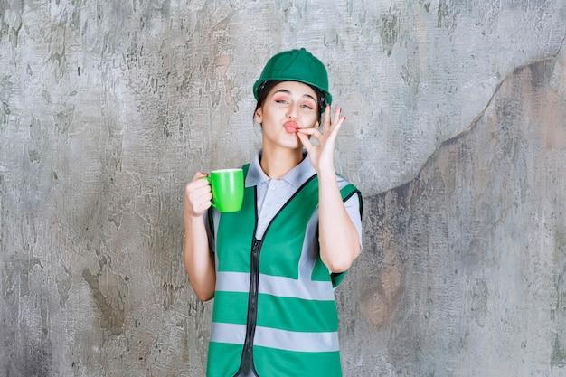 緑のコーヒーマグカップを保持し、楽しみのサインを示す緑のヘルメットの女性エンジニア