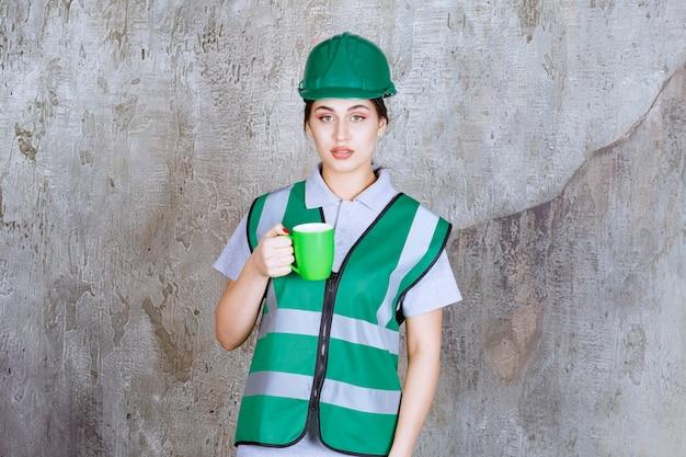 緑のコーヒーマグを保持している緑のヘルメットの女性エンジニア