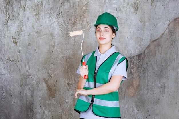 壁の絵のトリムローラーを保持している緑のヘルメットの女性エンジニア