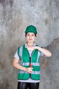 Женщина-инженер в зеленом шлеме держит обрезной валик для росписи стен