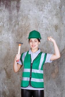 Женщина-инженер в зеленом шлеме держит топор с деревянной ручкой для ремонтных работ и показывает мышцы рук