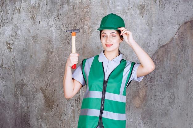 Женщина-инженер в зеленом шлеме держит топор с деревянной ручкой для ремонтных работ