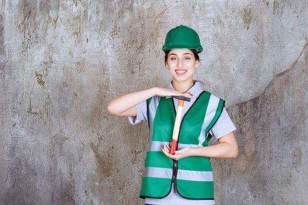 修理作業のために木製の柄の斧を持っている緑のヘルメットの女性エンジニア