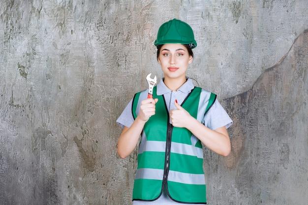 修理作業のための金属レンチを保持し、楽しみの手のサインを示す緑のヘルメットの女性エンジニア