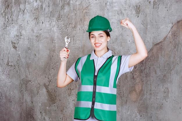 修理作業のための金属レンチを保持し、楽しみの手のサインを示す緑のヘルメットの女性エンジニア。