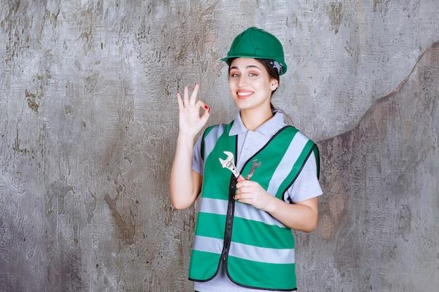 修理作業のための金属レンチを保持し、肯定的な手のサインを示す緑のヘルメットの女性エンジニア