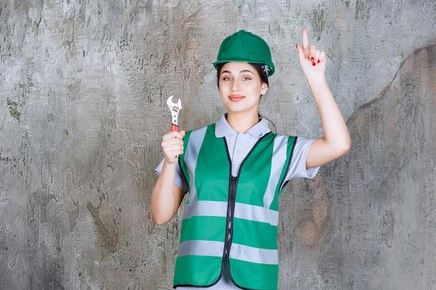 修理作業のための金属レンチを保持し、新しいアイデアを考えている緑のヘルメットの女性エンジニア