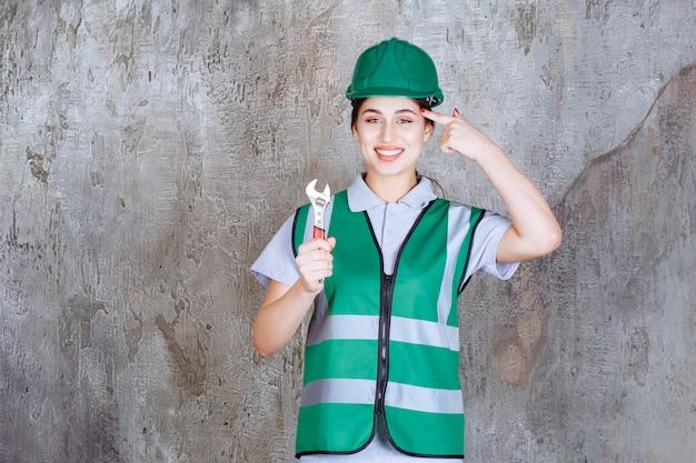 修理作業のための金属レンチを保持し、新しいアイデアを考えている緑のヘルメットの女性エンジニア。