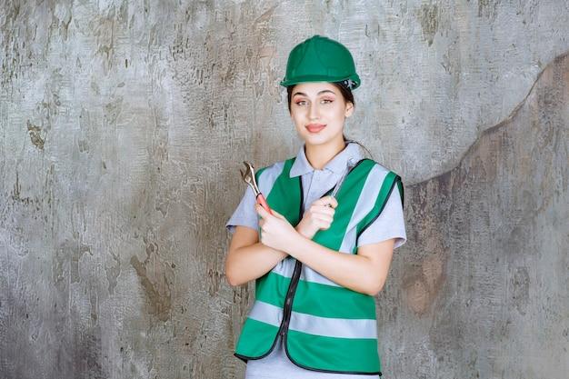 修理作業のための金属レンチを保持している緑のヘルメットの女性エンジニア。