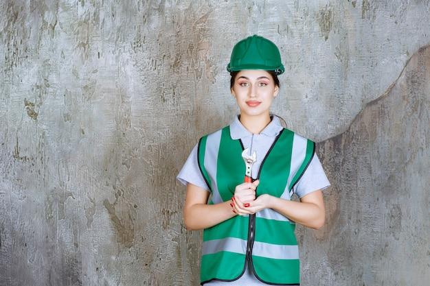 Женщина-инженер в зеленом шлеме держит металлический ключ для ремонтных работ