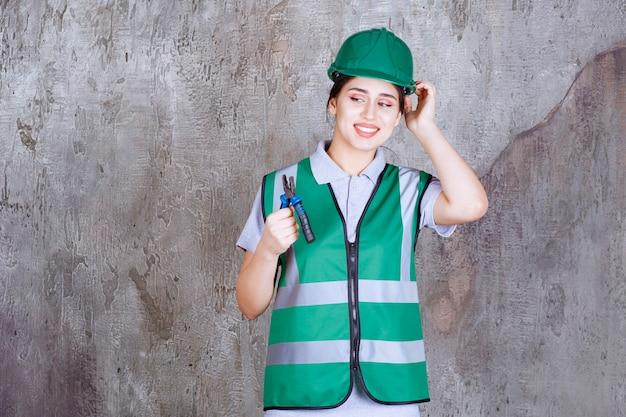 수리 작업을 위해 펜 치를 들고 녹색 헬멧에 여성 엔지니어가 혼란스럽고 사려 깊습니다.