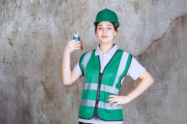 Женщина-инженер в зеленом шлеме, держащая плоскогубцы для ремонтных работ