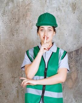 緑の制服とヘルメットをかぶった女性エンジニアが何も言わないように頼む。