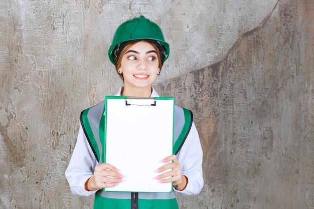 프로젝트 목록을 보여주는 녹색 유니폼과 헬멧에 여성 엔지니어.