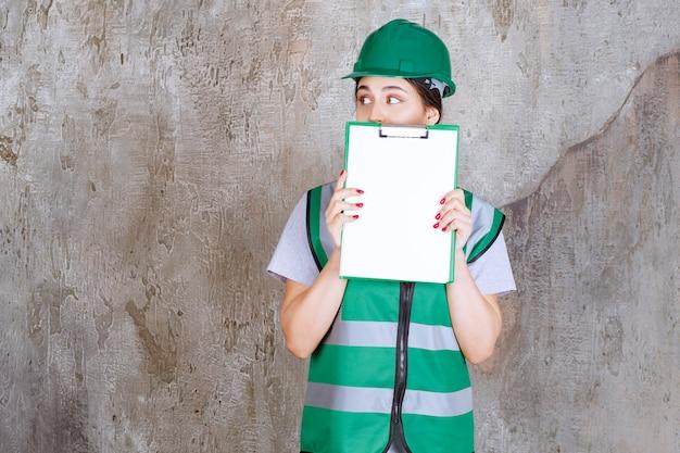プロジェクトシートを示す緑色のユニフォームとヘルメットを身に着けた女性エンジニアは、恐怖と恐怖に見えます。