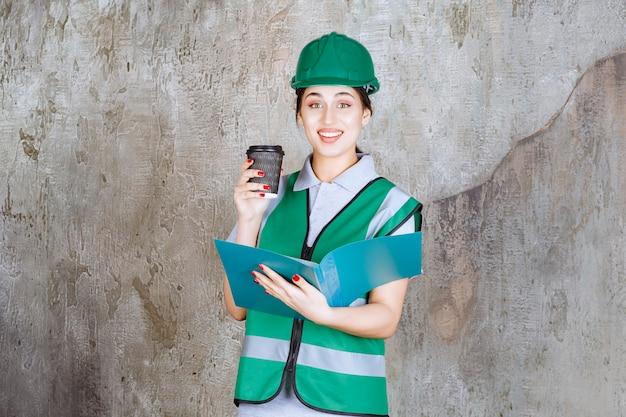 녹색 유니폼을 입고 헬멧을 쓴 여성 엔지니어는 블랙 커피 컵과 파란색 프로젝트 폴더를 들고 있습니다.