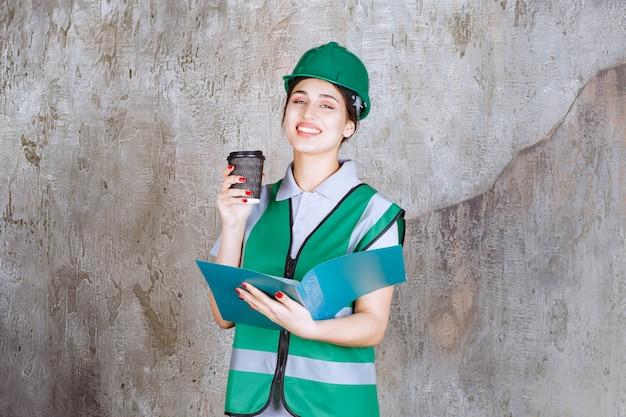 녹색 유니폼과 헬멧을 쓴 여성 엔지니어는 검은 커피 컵과 파란색 프로젝트 폴더를 들고 있습니다.
